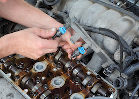 Car mechanic fixing fuel injector at two camshaft gasoline engine